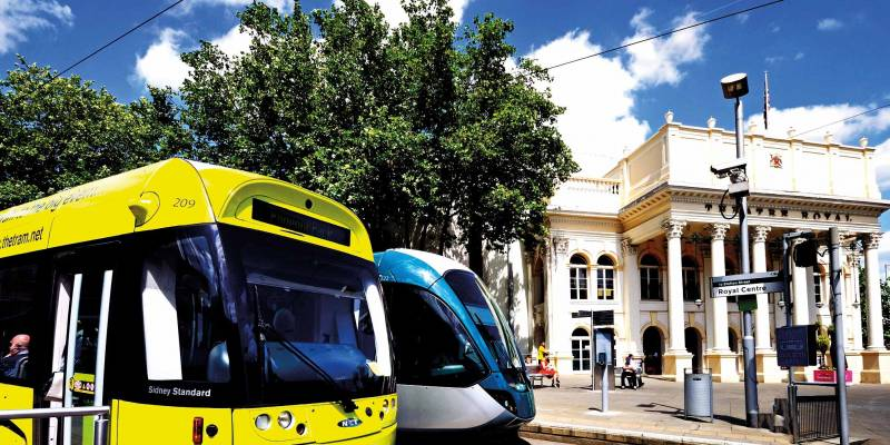 Two trams stationed at the Royal Centre stop with the front of the Theatre Royal in the background on a bright sunny day.