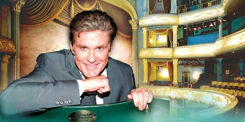 David Hasselhoff sits in the seat which bears his name with a shot of the entire Theatre Royal stage and seating in the background.
