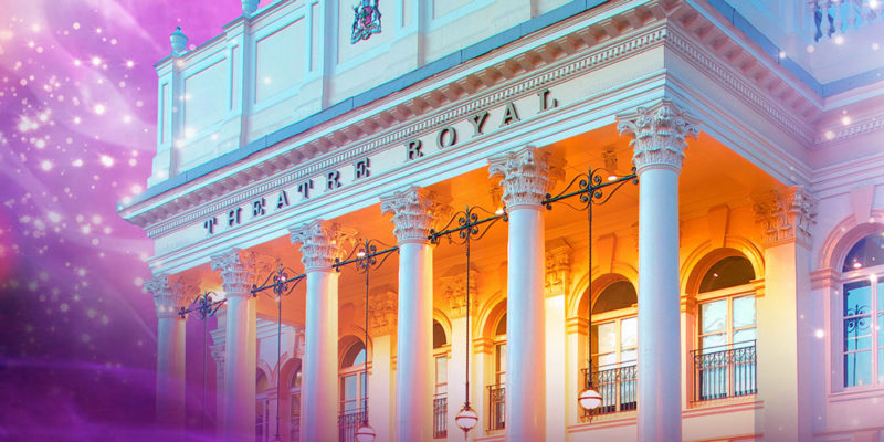 The front of the Theatre Royal with its iconic pillars. Lights illuminate the inside of the portico and give the theatre a magical quality.