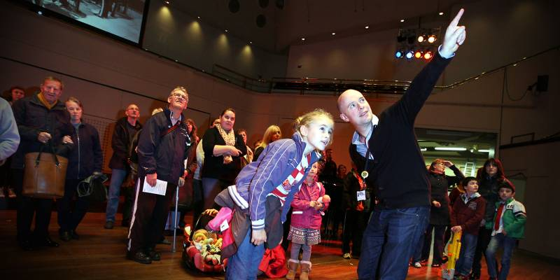 Visitors of all ages to the Royal Concert Hall stand on the stage and are shown around by a member of staff.