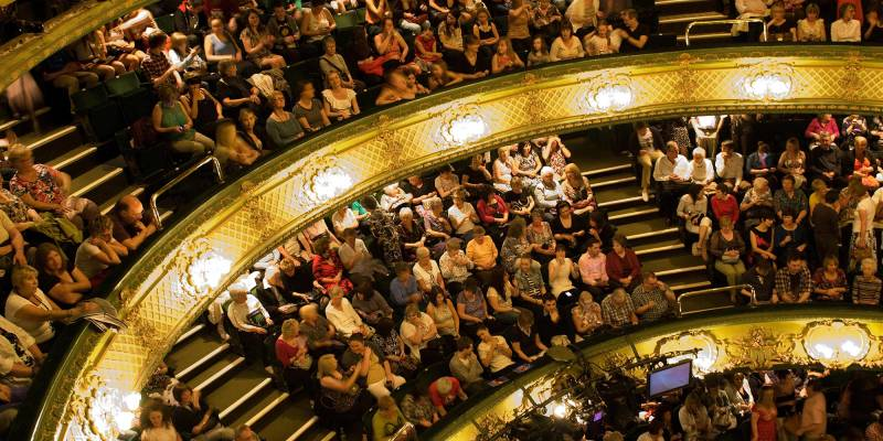 An overhead view of the upper circle, dress circle, and stalls in the Theatre Royal, where a wide range of people sit and chat excitedly about the show they are about to watch.