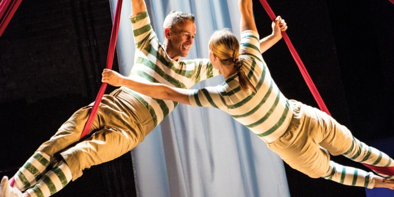 Two acrobats in stripey green outfits swing around together on ribbons suspended from above, staring into each other's eyes as they rotate.