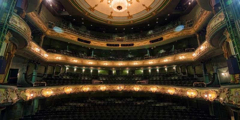 A shot of the Theatre Royal auditorium taken from the stage. The large chandelier hangs proudly from the ceiling and lights dotted around the auditorium highlight the wonderful green of the theatre and the intricate golden designs that decorate the different levels.