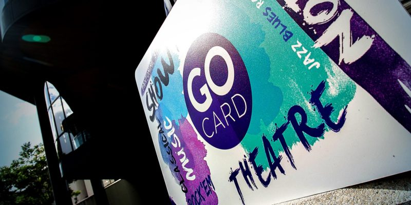 A Go Card (with its signature purple and turquoise paint streaks and circular logo) sits just outside the Royal Concert Hall's doors.