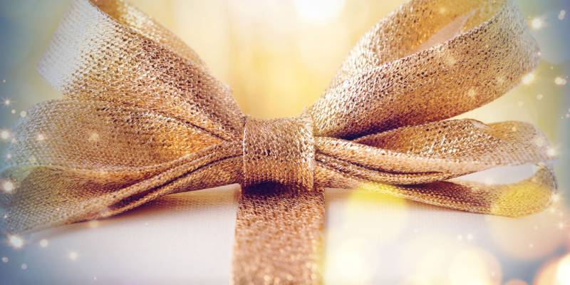A golden bow sitting on top of a white present with the golden ribbon wrapped around it is surrounded by sparkles.