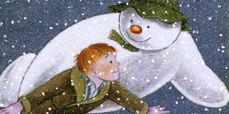 The Snowman in his signature green cap and scarf with his red button nose flies through the night sky alongside the red-headed boy in his green dressing gown.