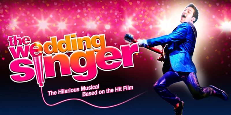 A man in a blue suit jumping while holding an electric guitar. The Wedding Singer Tickets