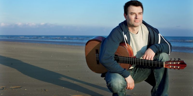 Craig Ogden in a blue hoodie and jeans crouches on a beach holding his guitar with the sea behind him.