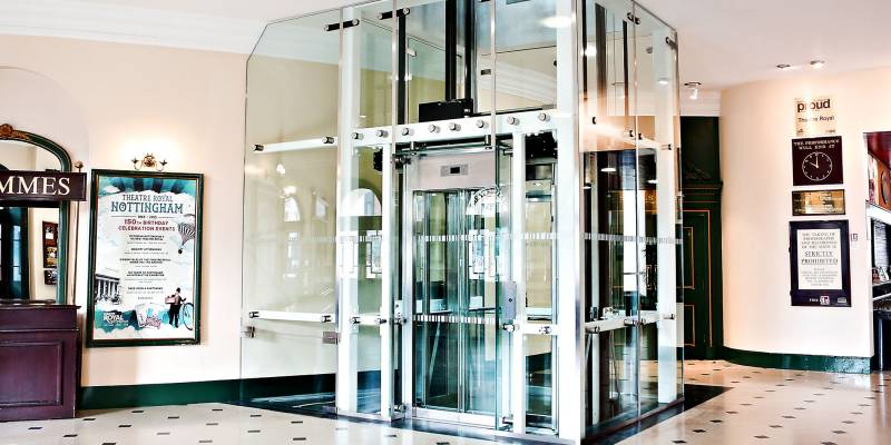 A glass lift in the Theatre Royal foyer located in between the Programmes stand and the doors to Stalls Right.