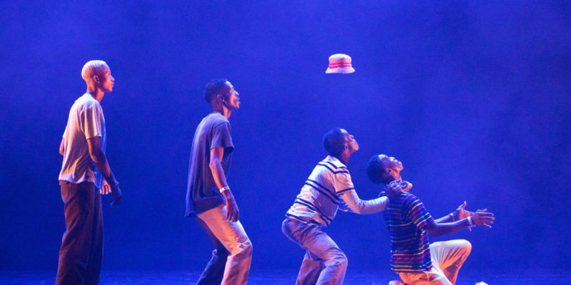 Four members of the Soweto Skeleton Movers are standing in a line. From left to right, each person is standing lower than the person next to him. A hat flies through the air to land on one of the dancer's heads for Breakin' Convention.