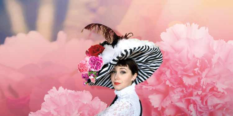 An elegant woman in a long-sleeved and ruffled white lace dress with a large zebra print hat covered with flowers and feathers sits elegantly in front of large pink flowers for My Fair Lady.