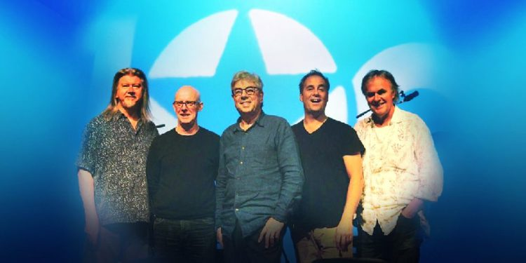 The five members of 10cc stand in front of a blue background bearing a large version of their logo.
