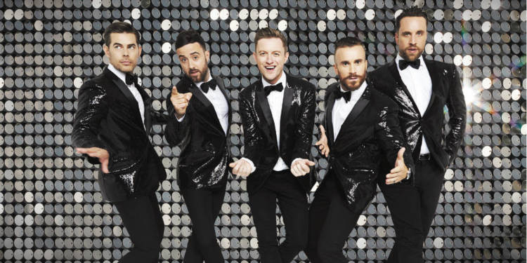 The Overtones, dressed in black sequined suit jackets with white shirts and bow ties, pose in front of a silver sequined background.